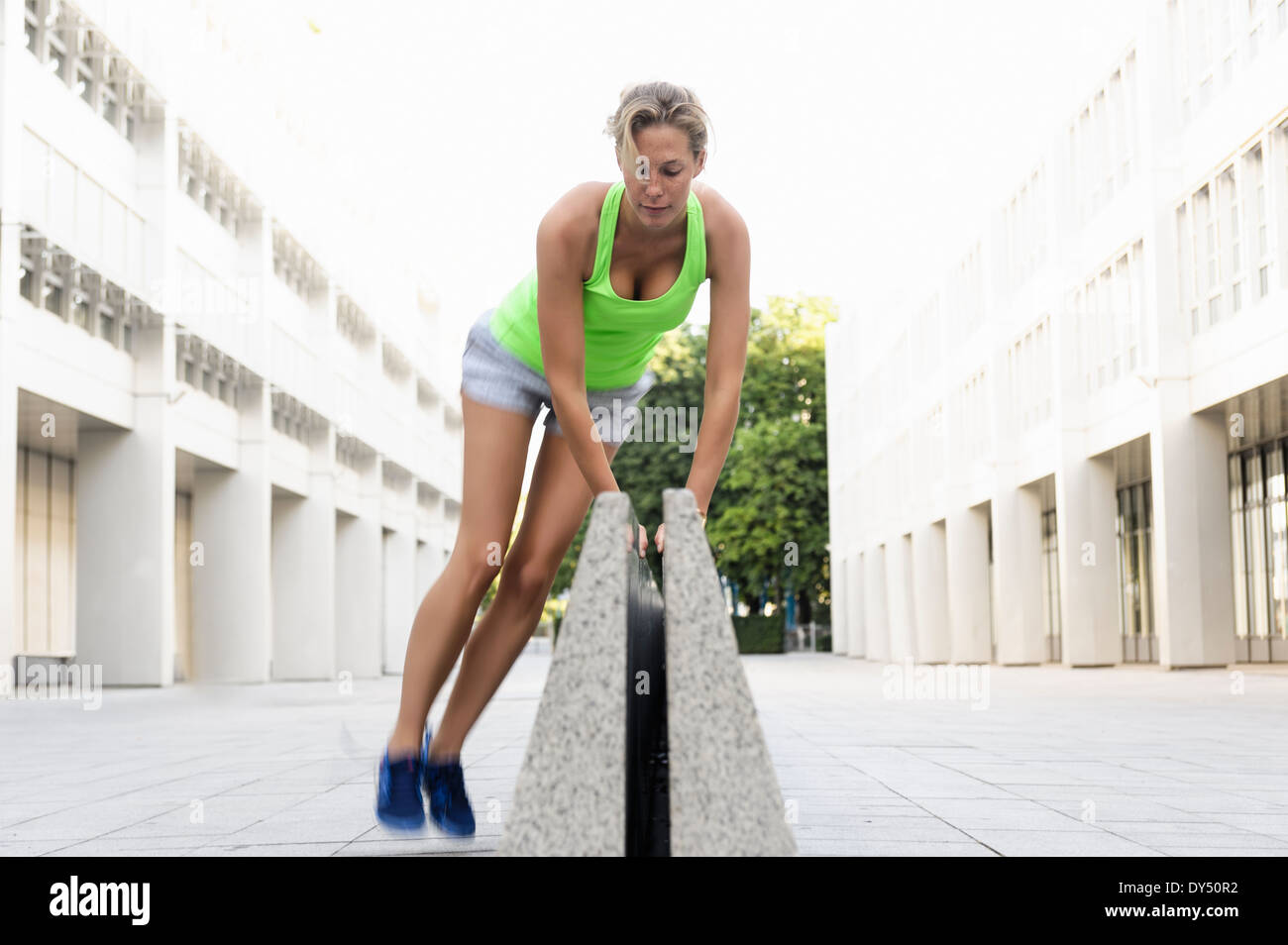 Young woman jumping over divider - Stock Image