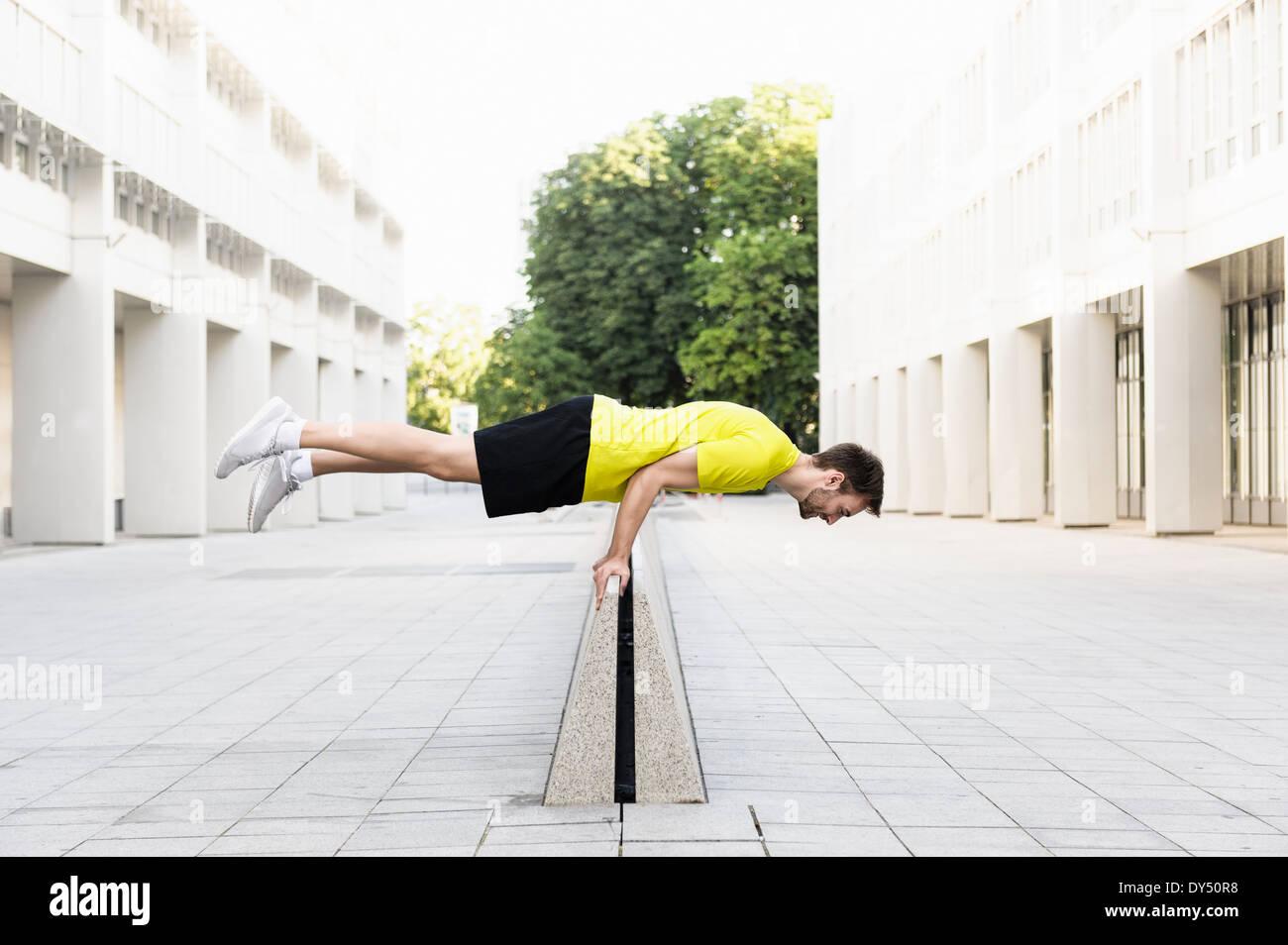 Young man balancing horizontally on divider - Stock Image