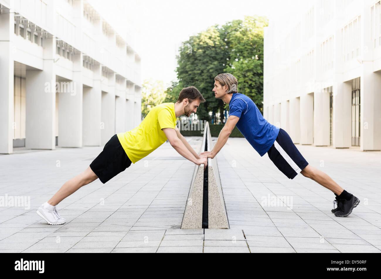 Men stretching on divider - Stock Image