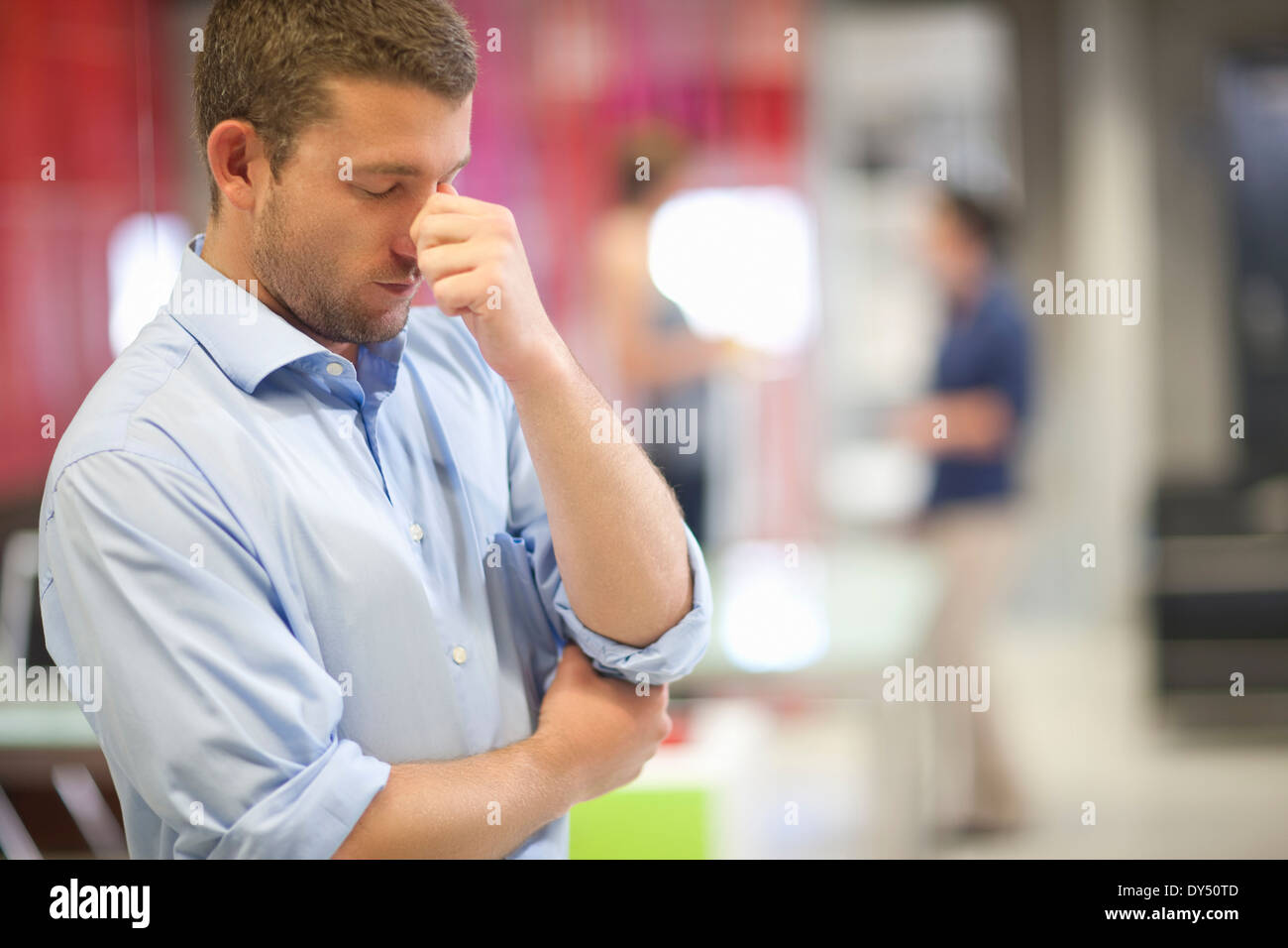 Young businessman looking stressed in office - Stock Image