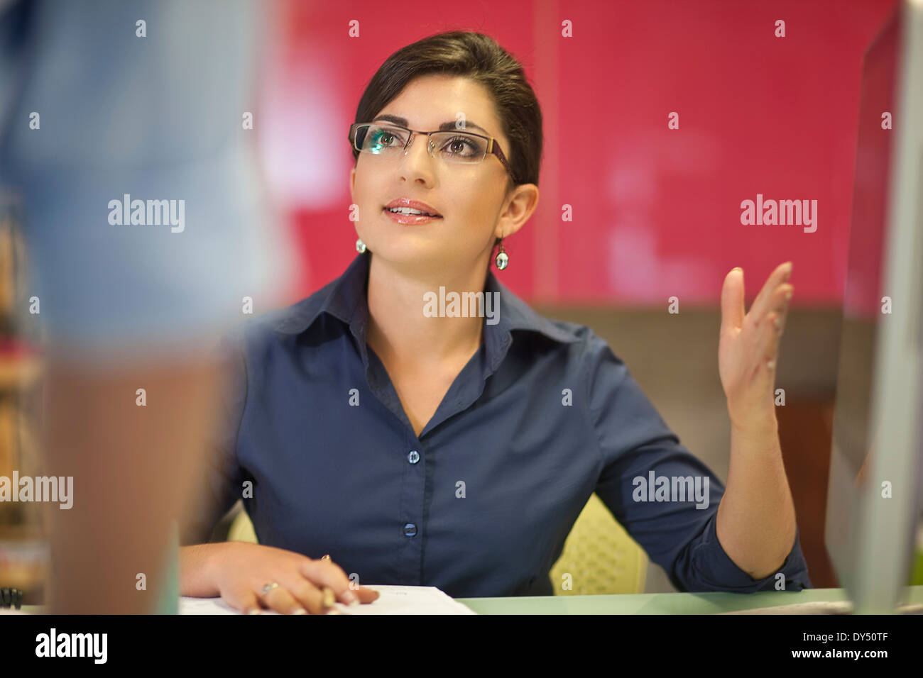 Young businesswoman advising colleague in office - Stock Image