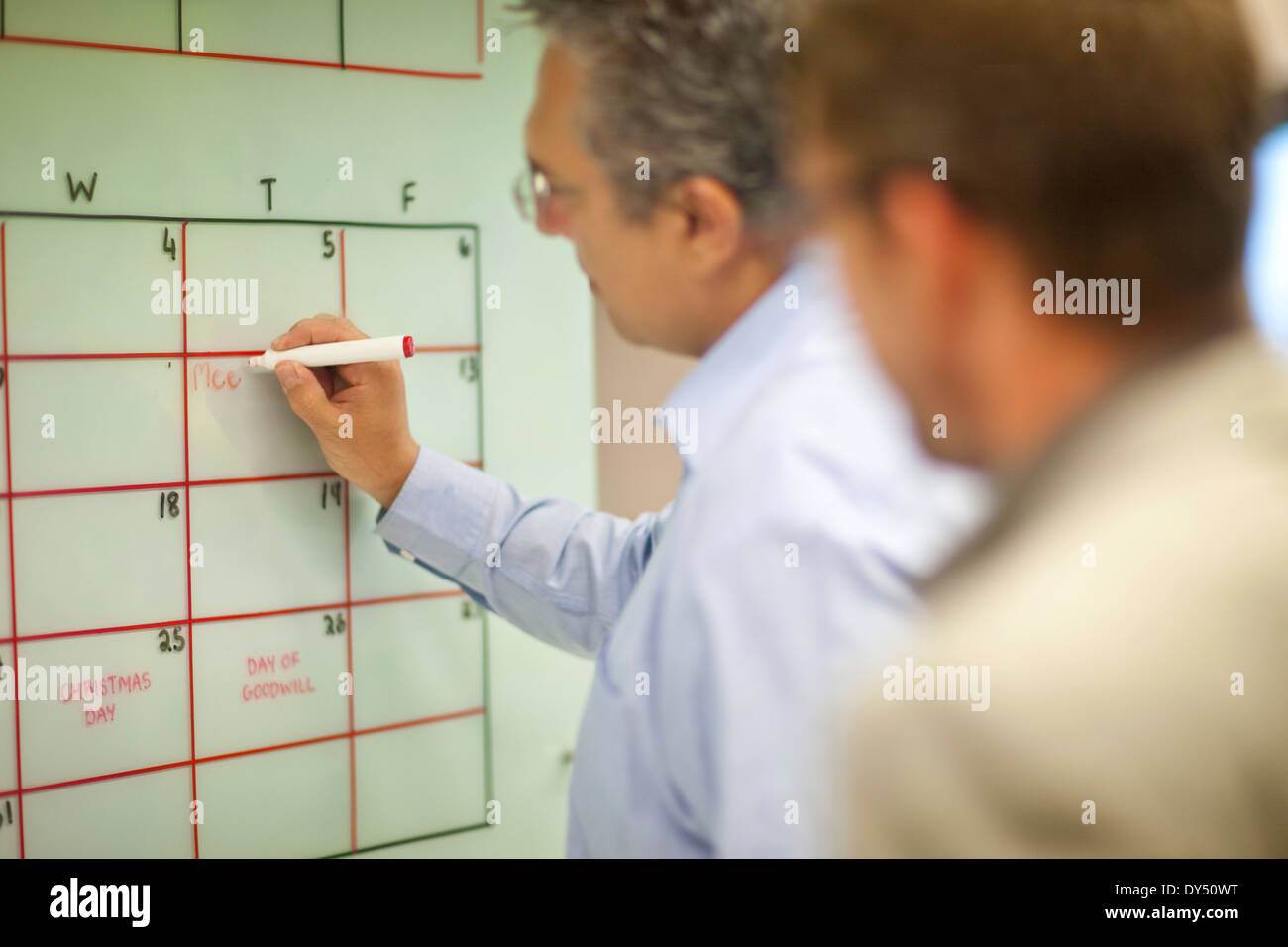 Mature businessman organizing timetables in office - Stock Image
