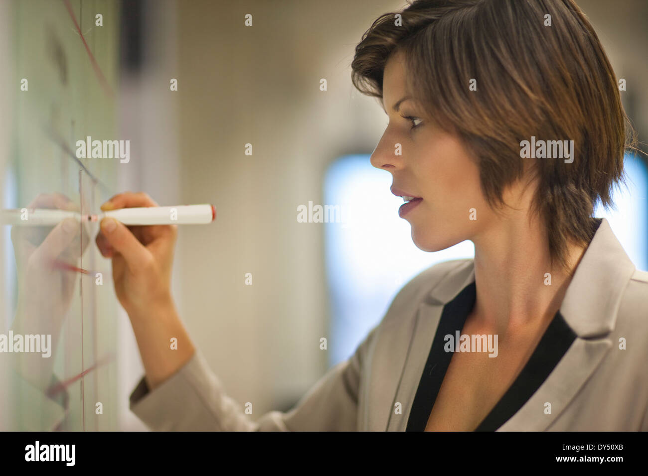 Young businesswoman organizing timetables in office - Stock Image