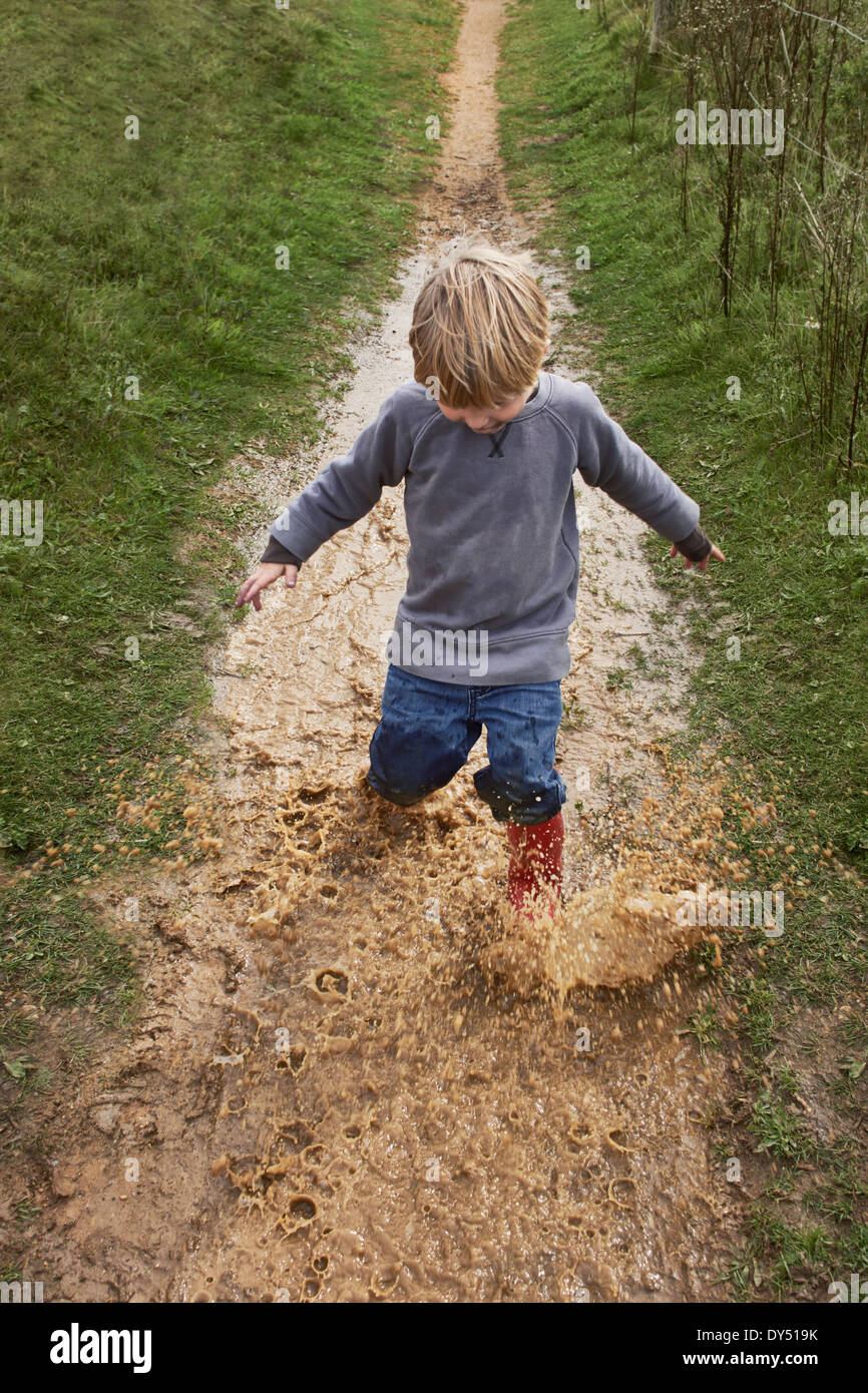 Boy splashing through muddy puddle - Stock Image
