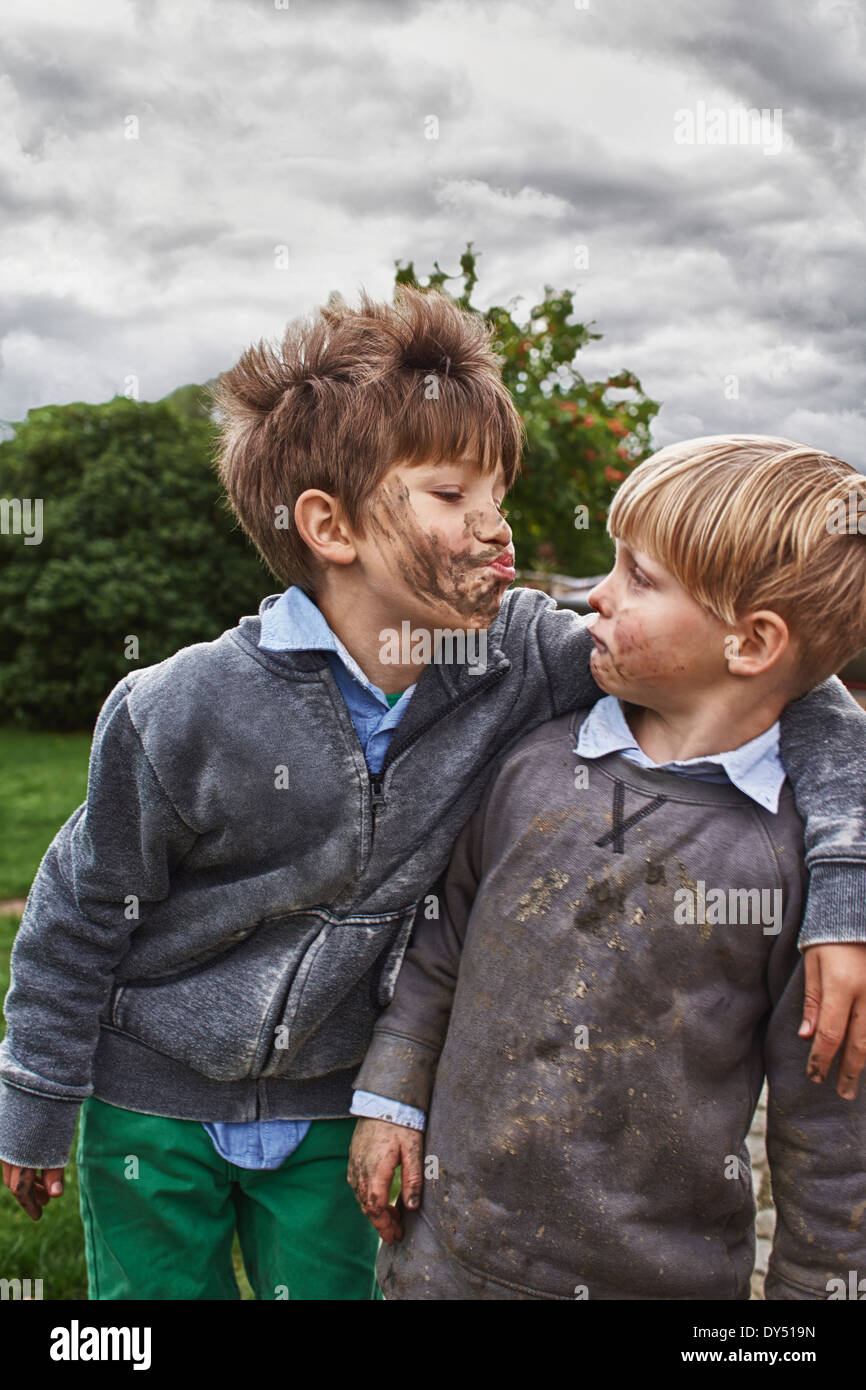 Brothers with muddy faces, arm around - Stock Image