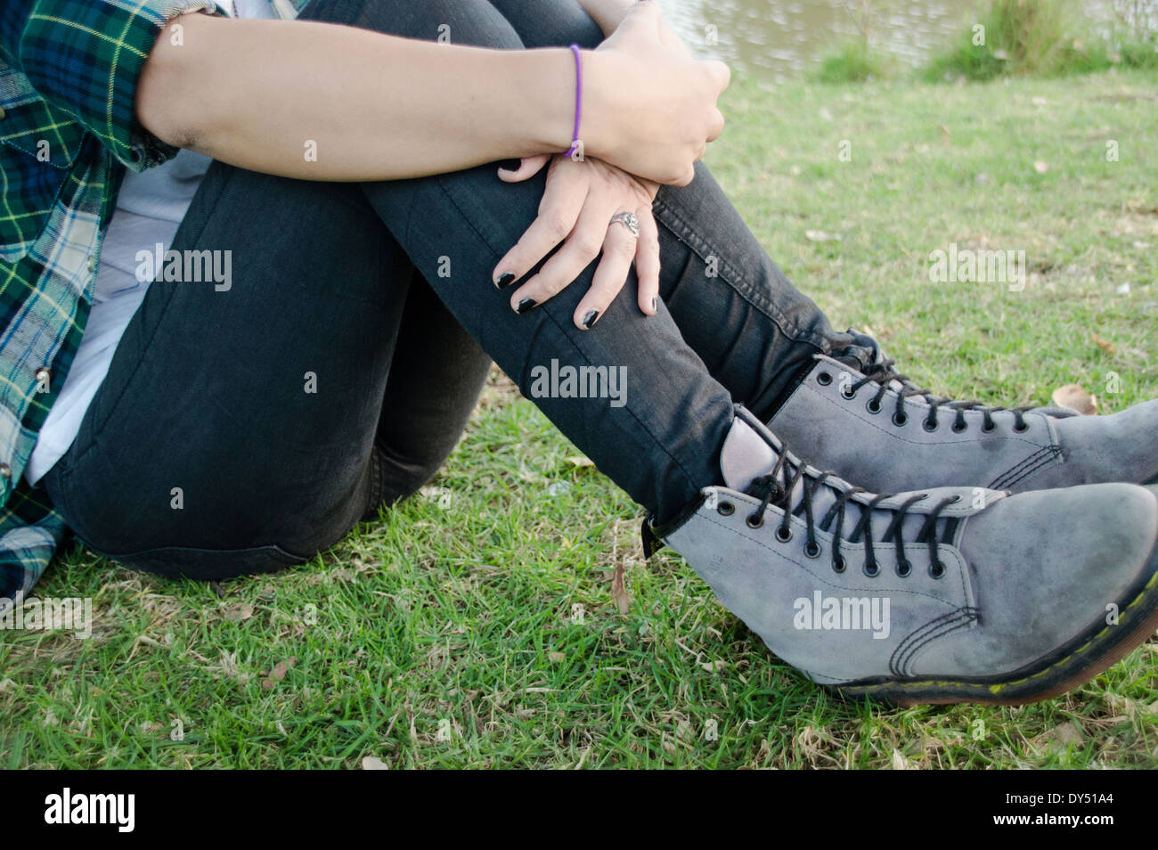 Waist down, young woman sitting on grass Stock Photo