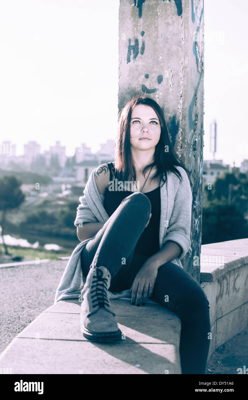 Young woman sitting on wall - Stock Image