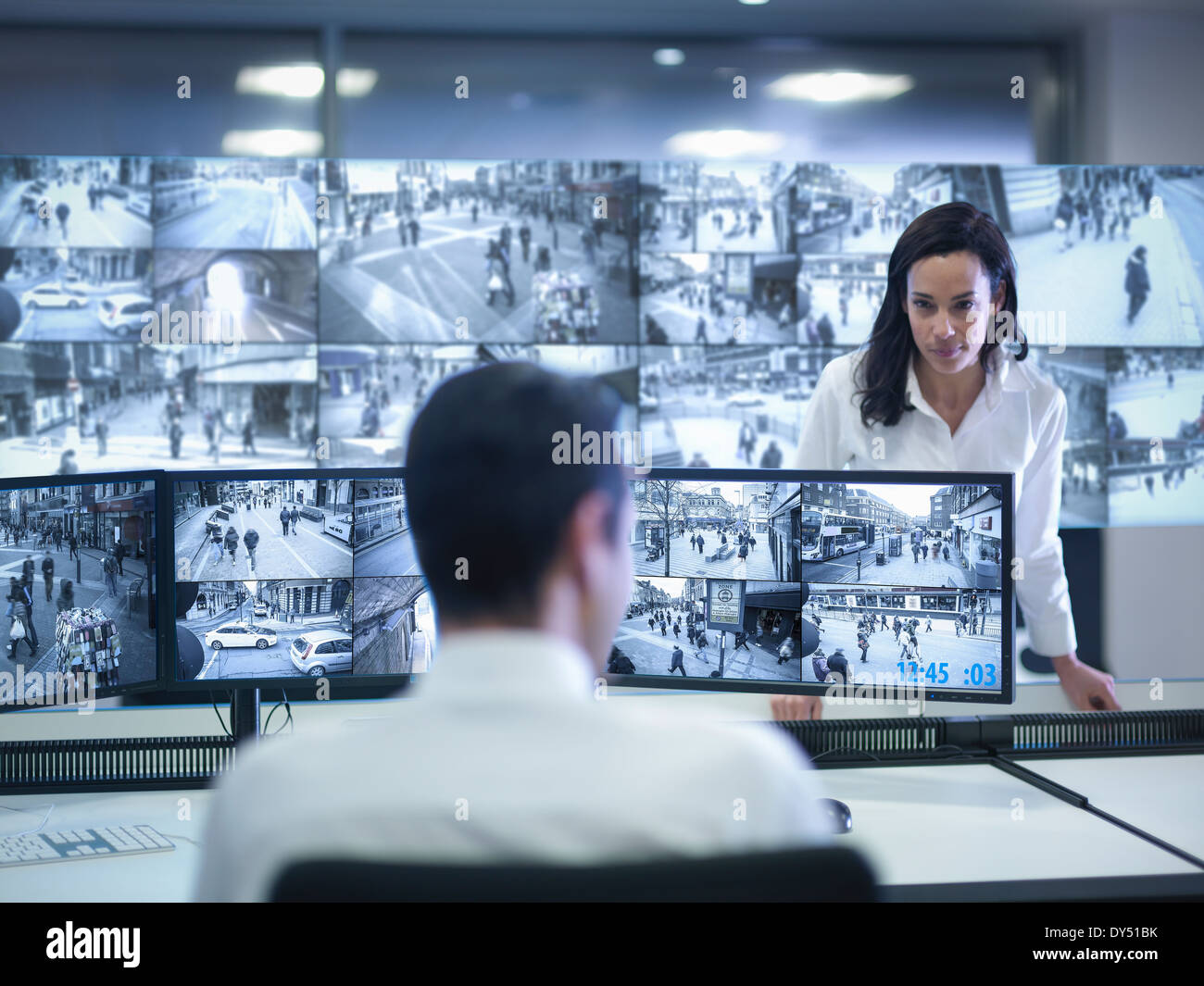 Security guards working at CCTV screens in control room - Stock Image