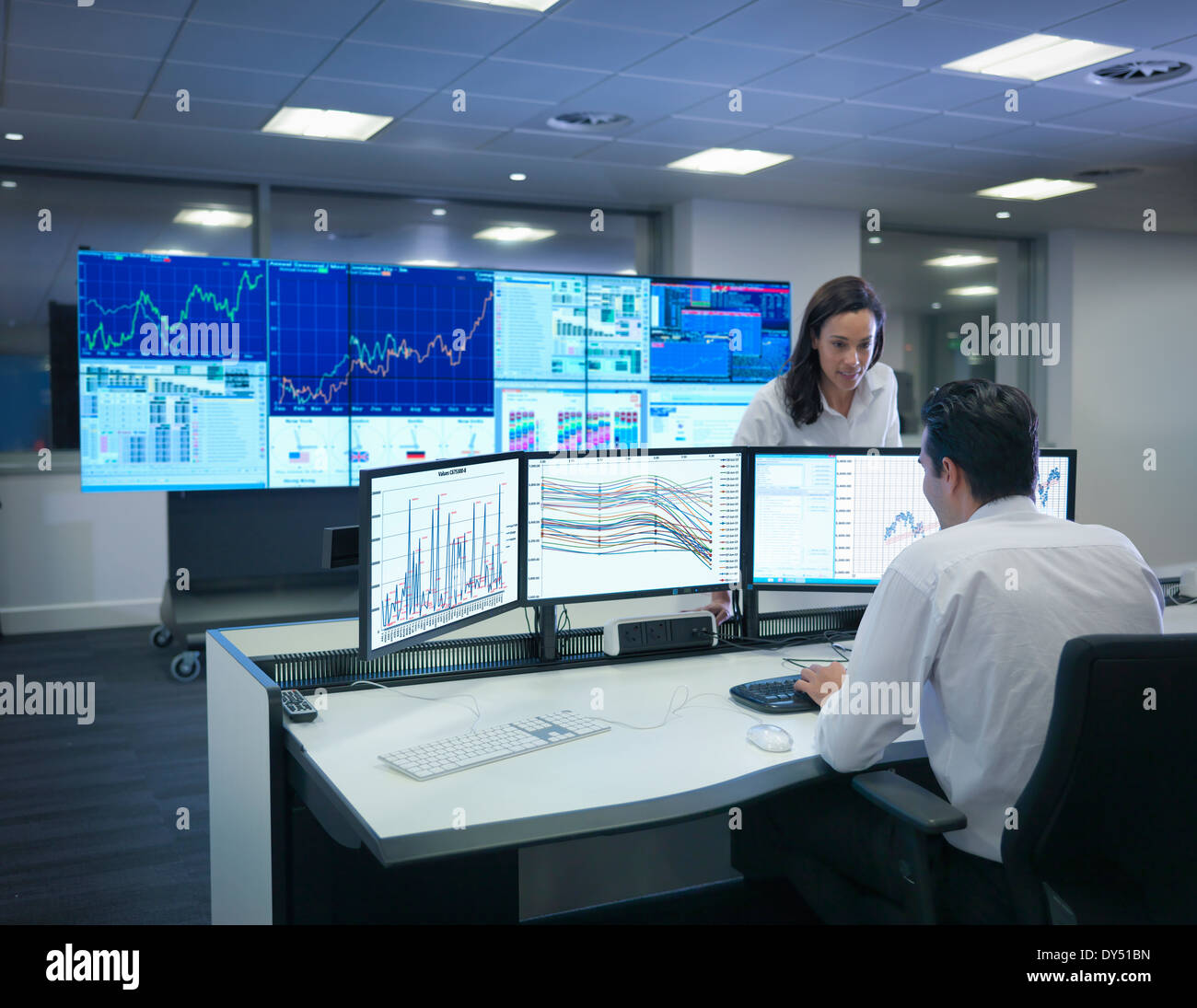 Financial analysts working with graphs on screens in control room - Stock Image