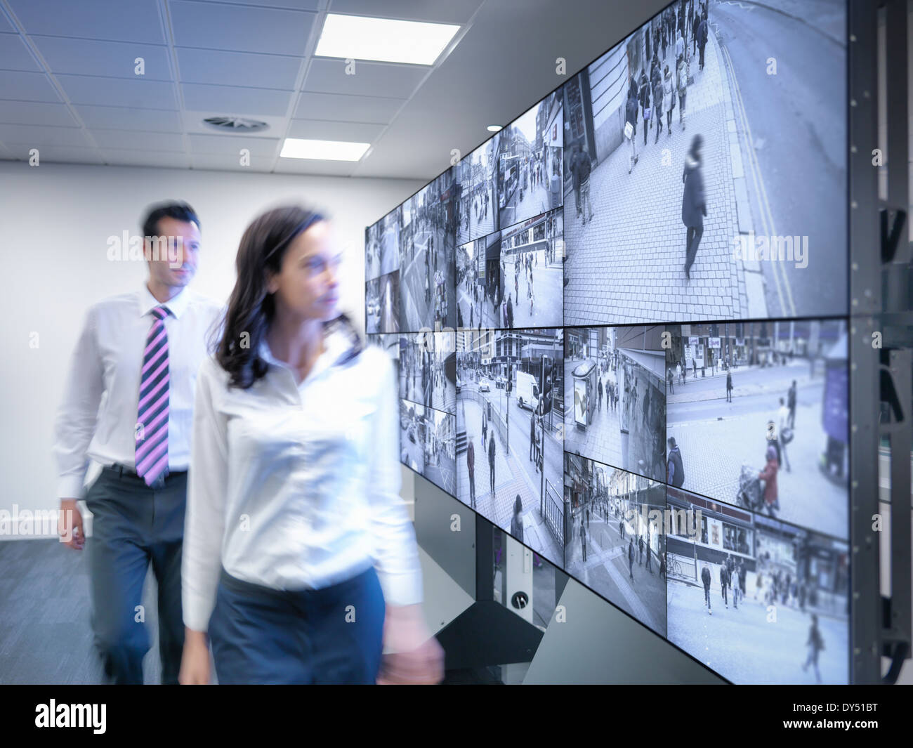 Security workers walking past CCTV screens in control room - Stock Image
