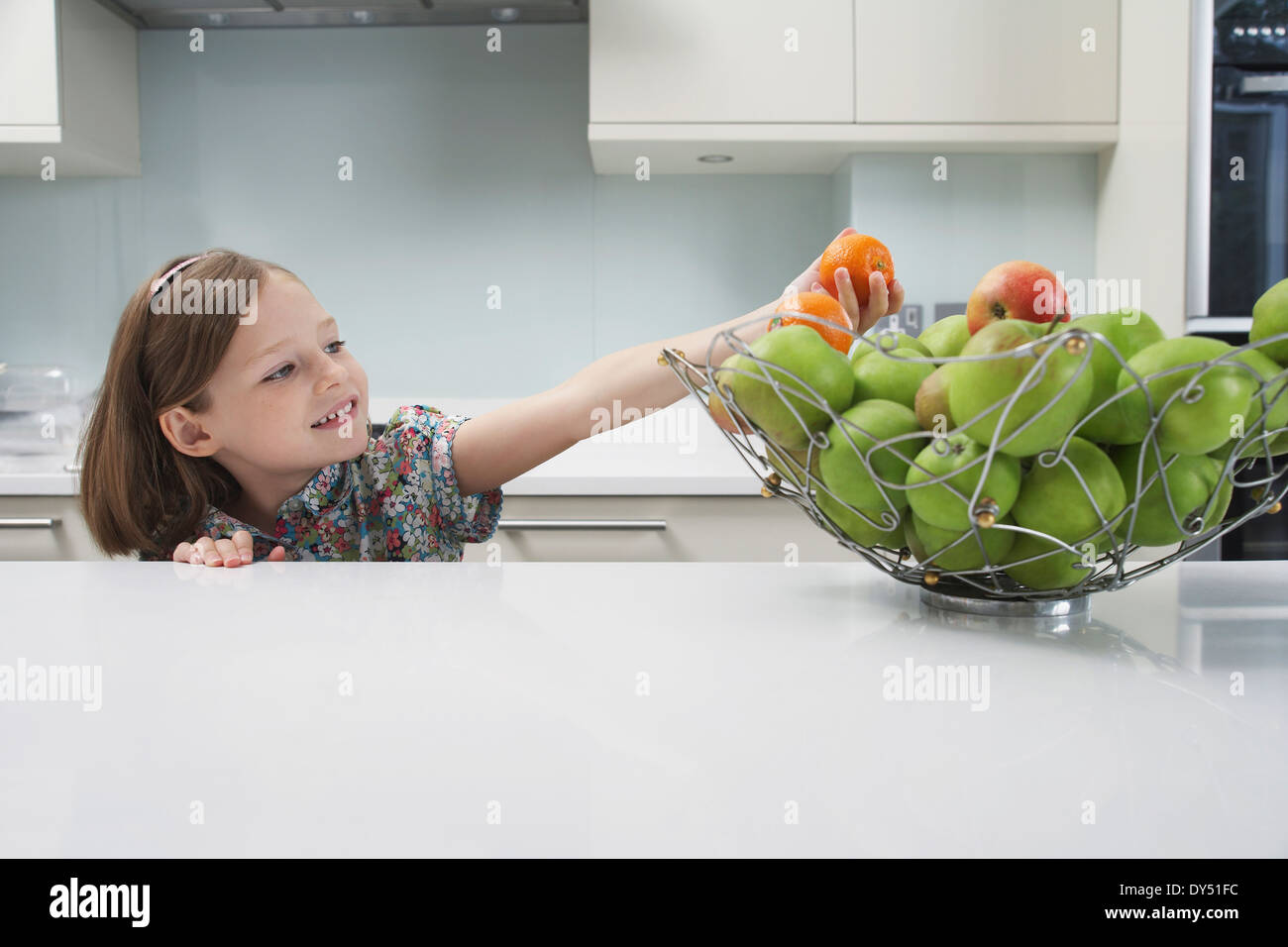 Young girl reaching for a tangerine from the fruit bowl - Stock Image