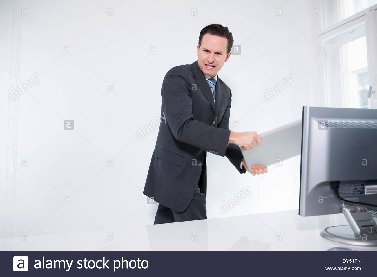 Businessman carrying off laptop from office - Stock Image