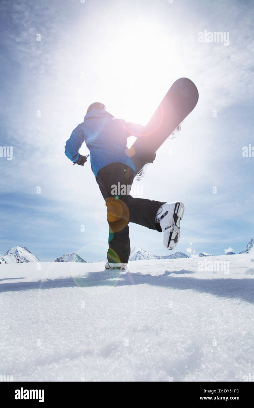 Mature man carrying his snowboard uphill, Obergurgl, Austria - Stock Image