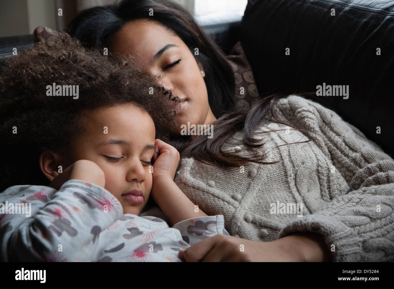 Two sisters asleep on sofa - Stock Image