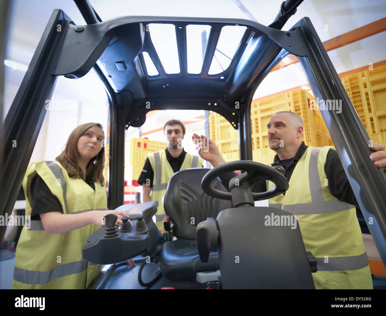 Instructor showing apprentices controls of forklift truck - Stock Image