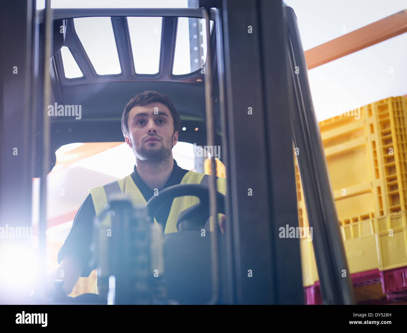 Apprentice drives forklift truck in training facility - Stock Image