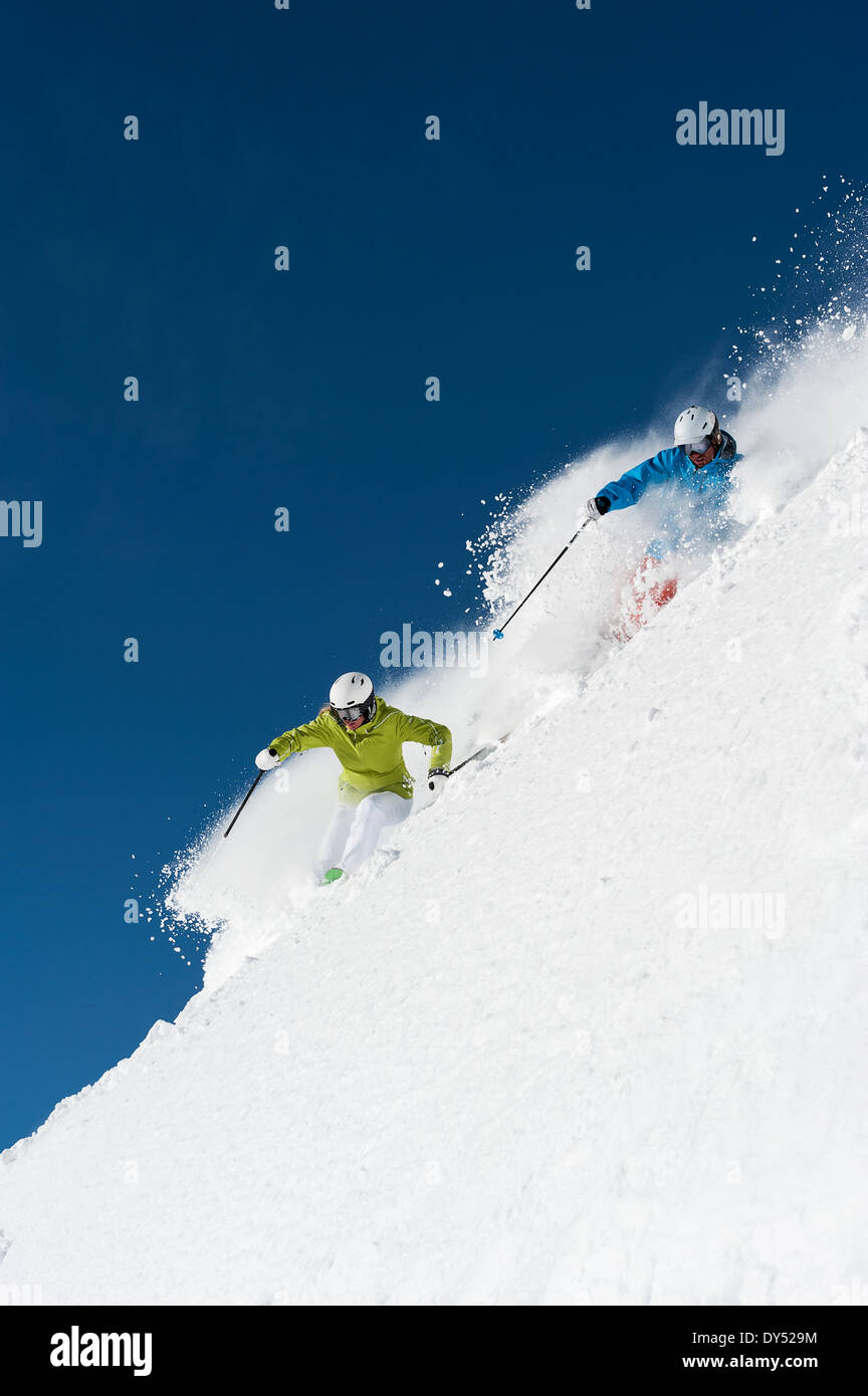 Male and female skiers racing downhill, Obergurgl, Austria - Stock Image