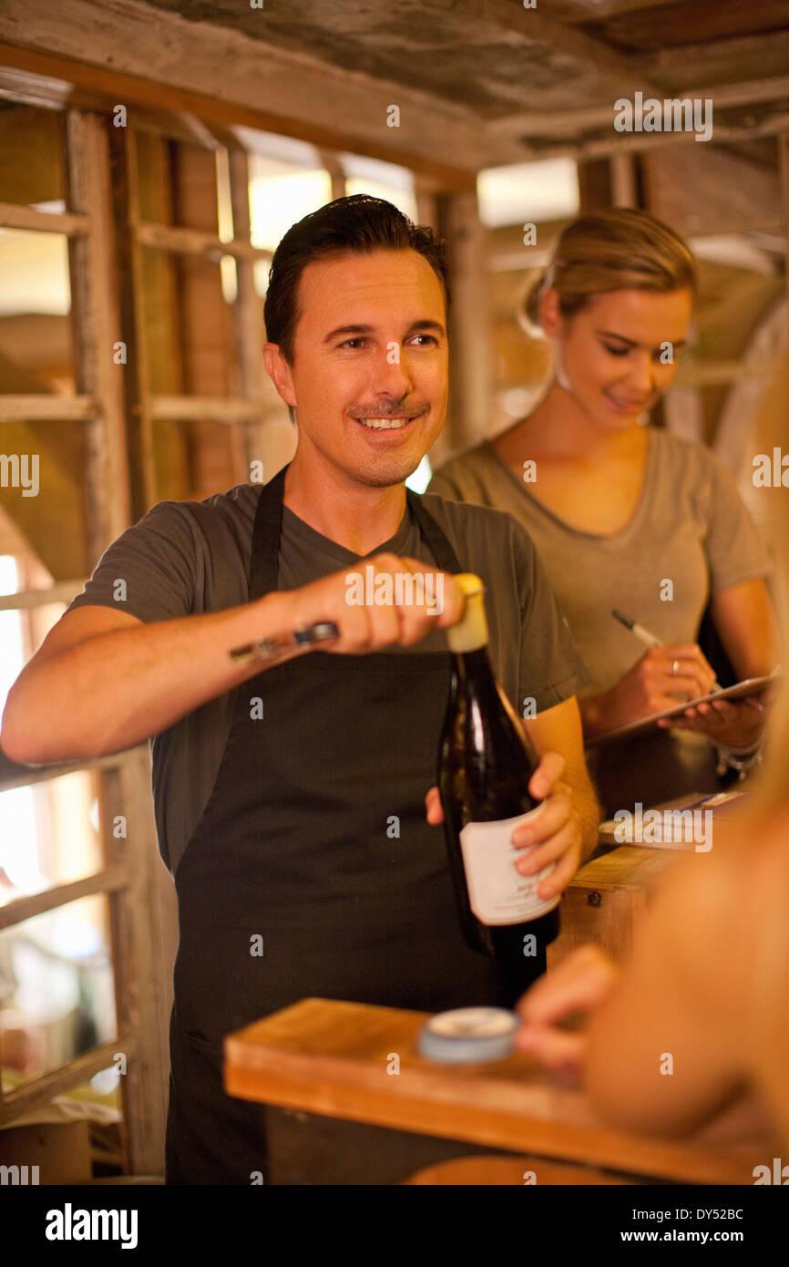 Sommelier opening bottle of wine in wine shop - Stock Image