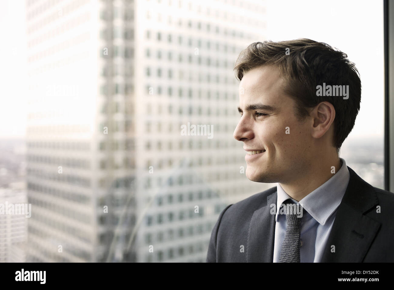 Portrait of young businessman looking out of office window - Stock Image
