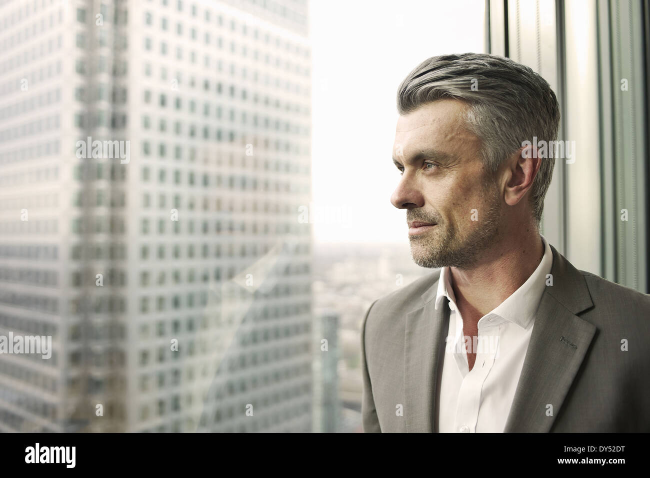 Portrait of mature businessman looking out of office window - Stock Image