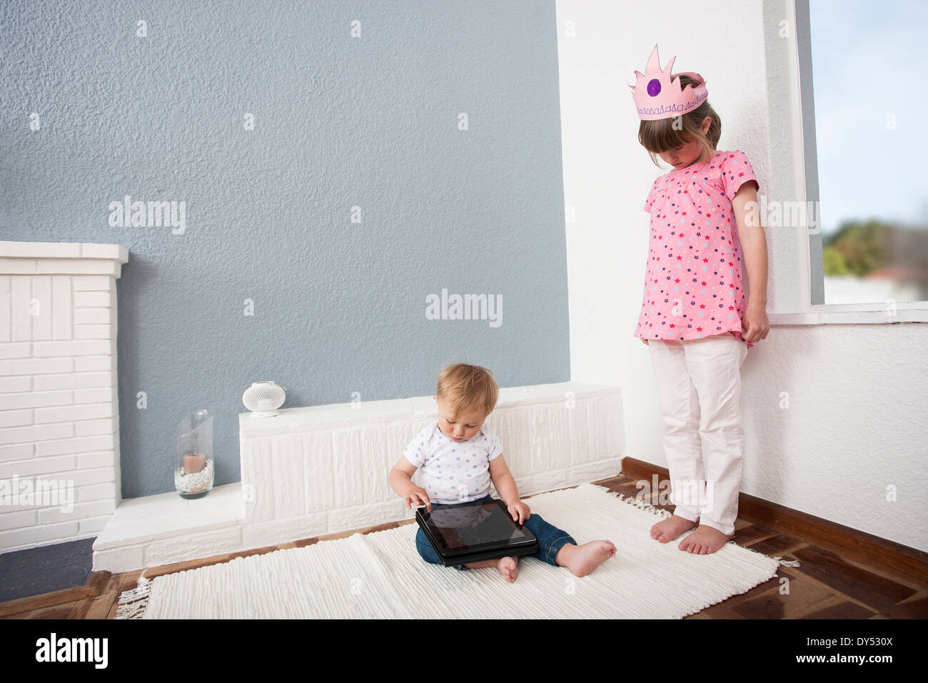 Girl watching over baby boy playing digital tablet Stock Photo
