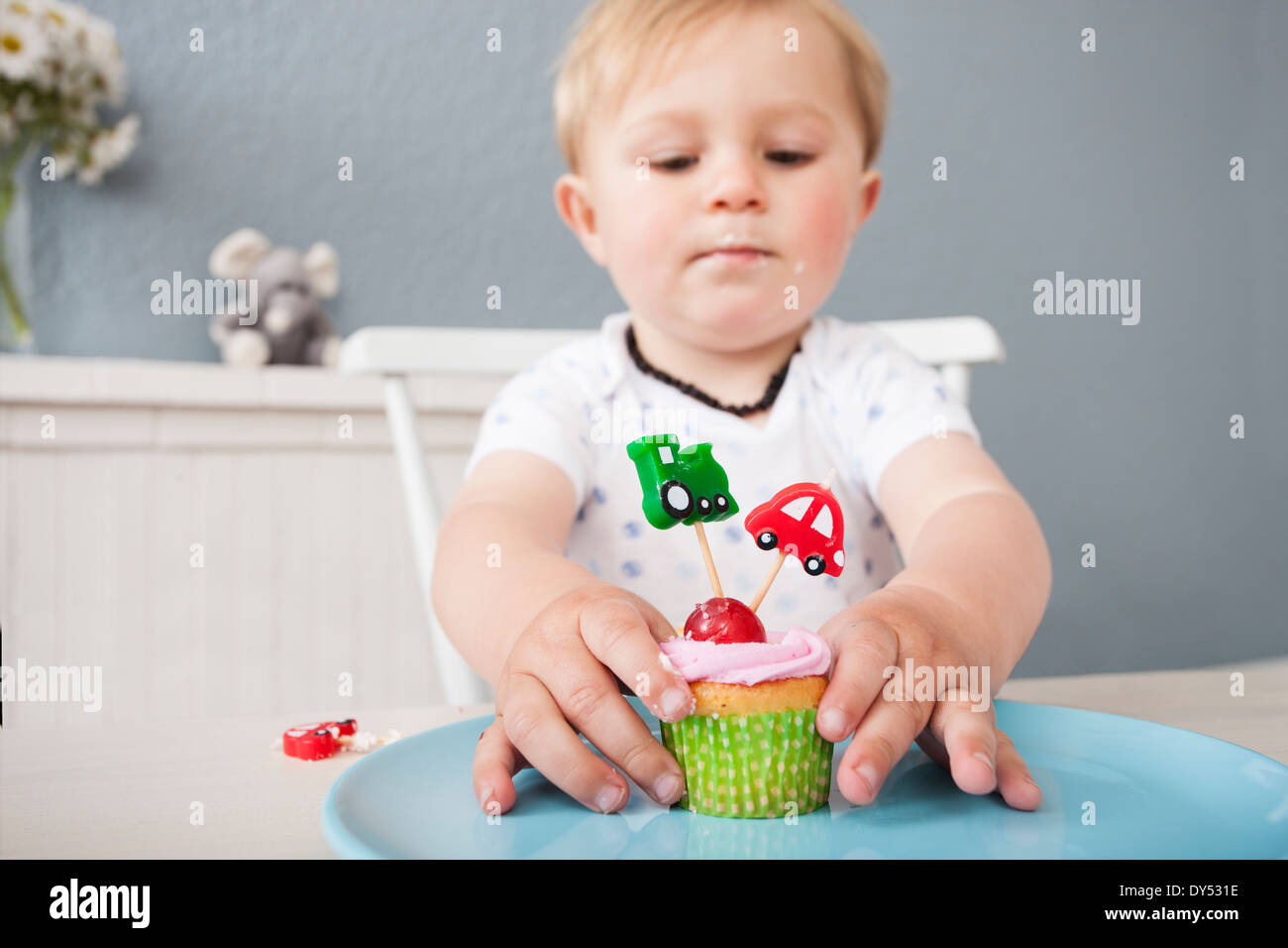 Baby boy playing with cupcake - Stock Image