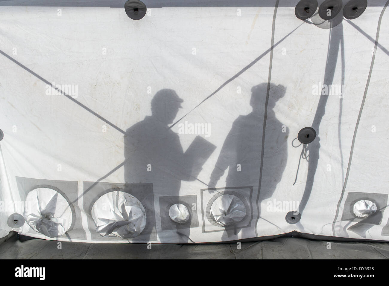Silhouette of Emergency Response Team workers inside control centre tent - Stock Image