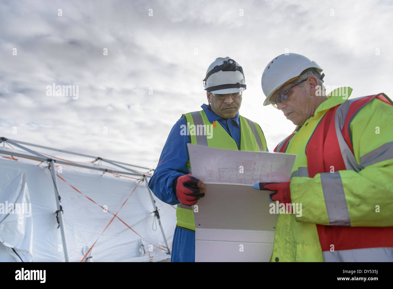 Emergency Response Team workers looking at plans - Stock Image