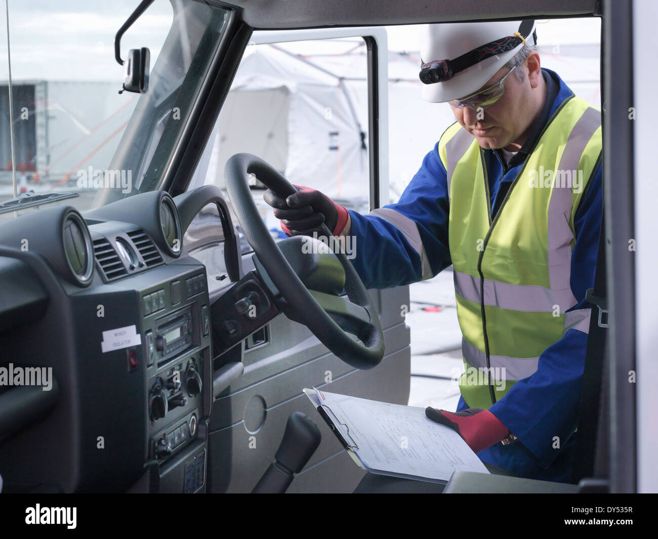 Emergency Response Team worker looking at notes in four wheel drive vehicle - Stock Image