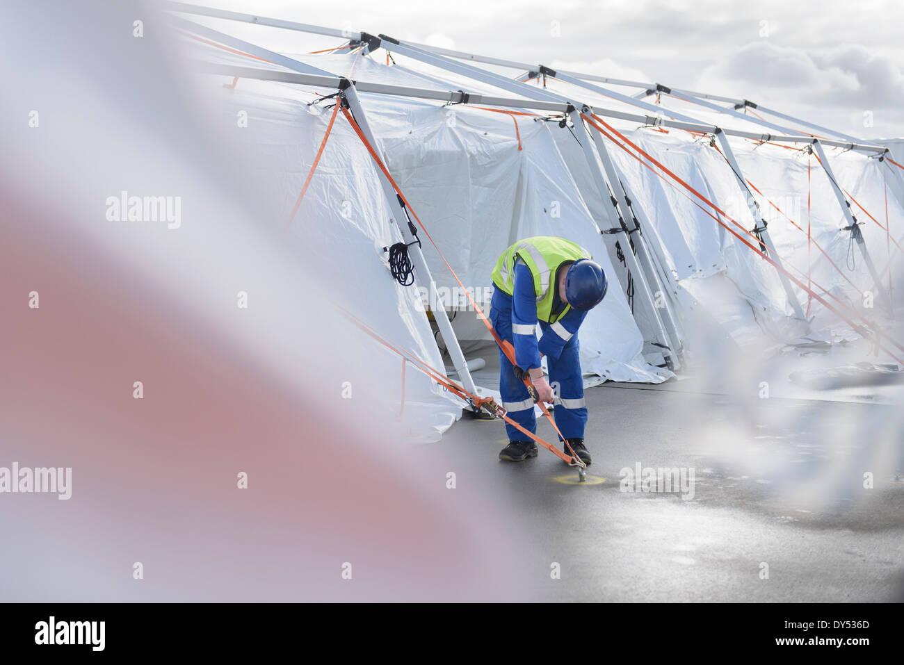 Emergency Response Team worker adjusting tent anchor - Stock Image