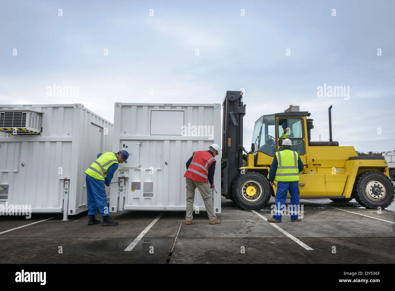 Emergency Response Team workers installing emergency control rooms with fork lift truck - Stock Image