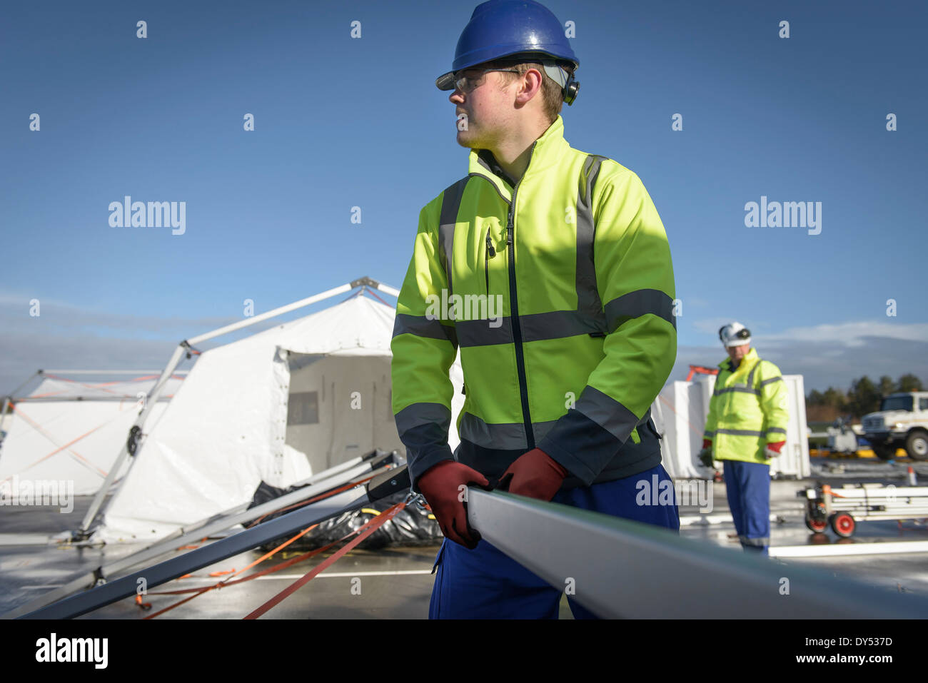 Emergency Response Team workers erecting tent control centre - Stock Image