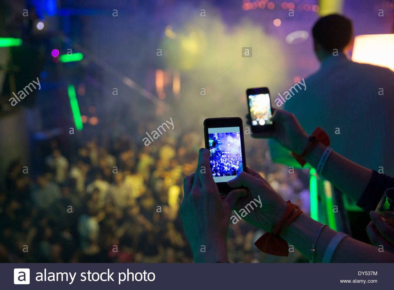 Women taking photograph in nightclub with cellular phone - Stock Image