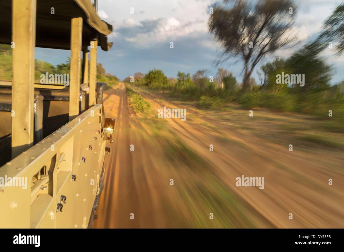 Safari truck speeding along dirt road, Kasane, Chobe National Park, Botswana, Africa - Stock Image