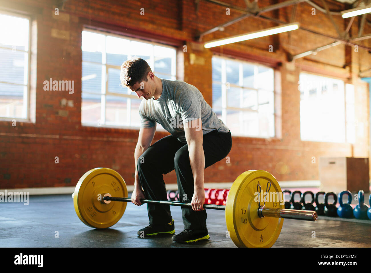Man lifting weights in gymnasium - Stock Image