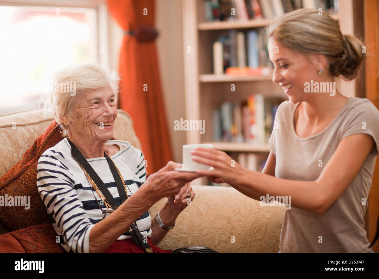 Care assistant handing coffee cup to senior woman - Stock Image
