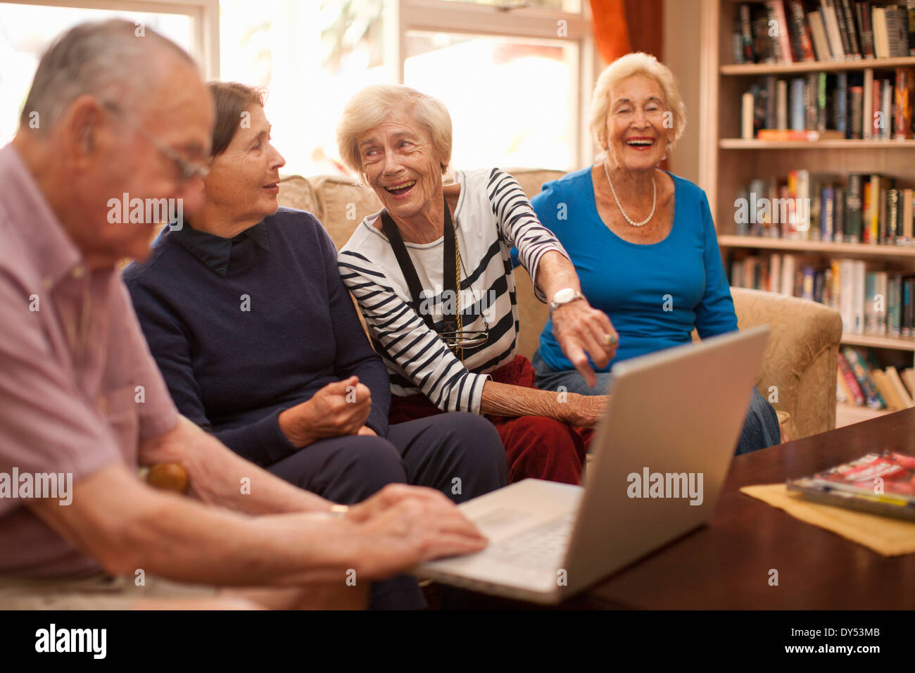 Senior man and female companions in retirement villa - Stock Image