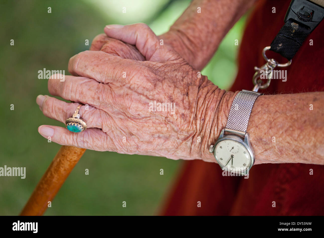 Close up of senior woman's hands holding walking stick Stock Photo