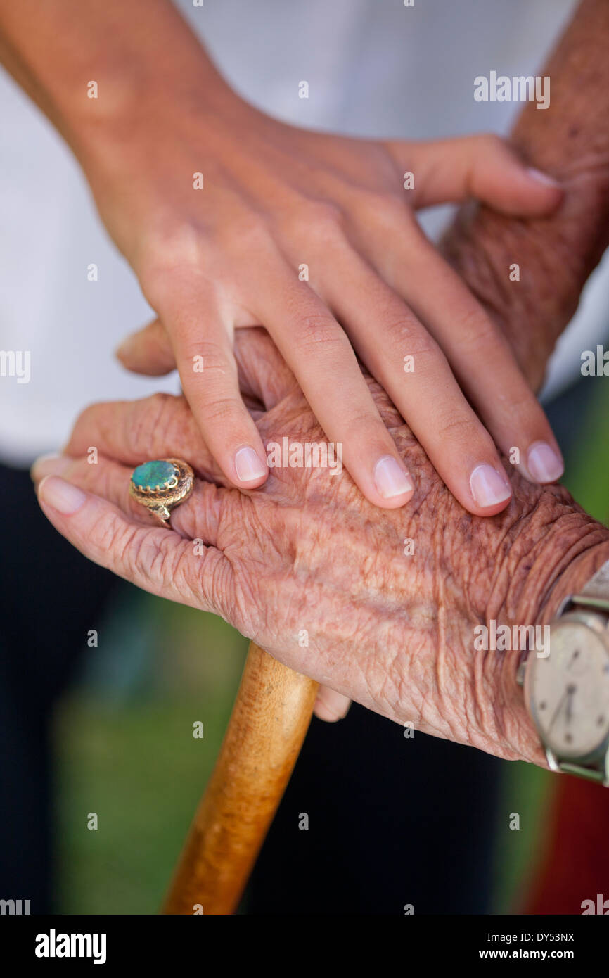 Close up of care assistants hand reassuring senior woman Stock Photo