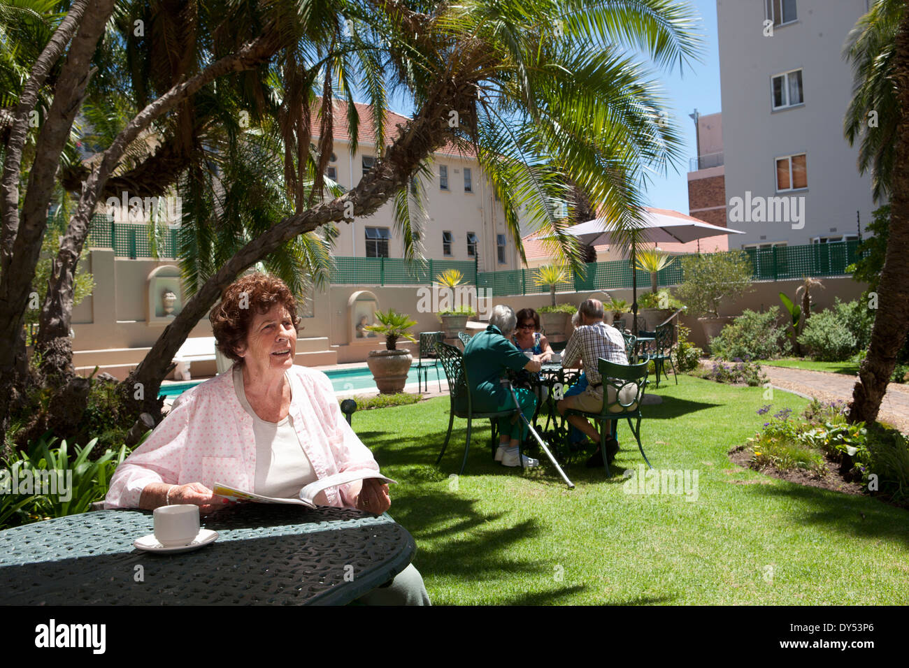 Senior woman having coffee in garden of retirement villa - Stock Image