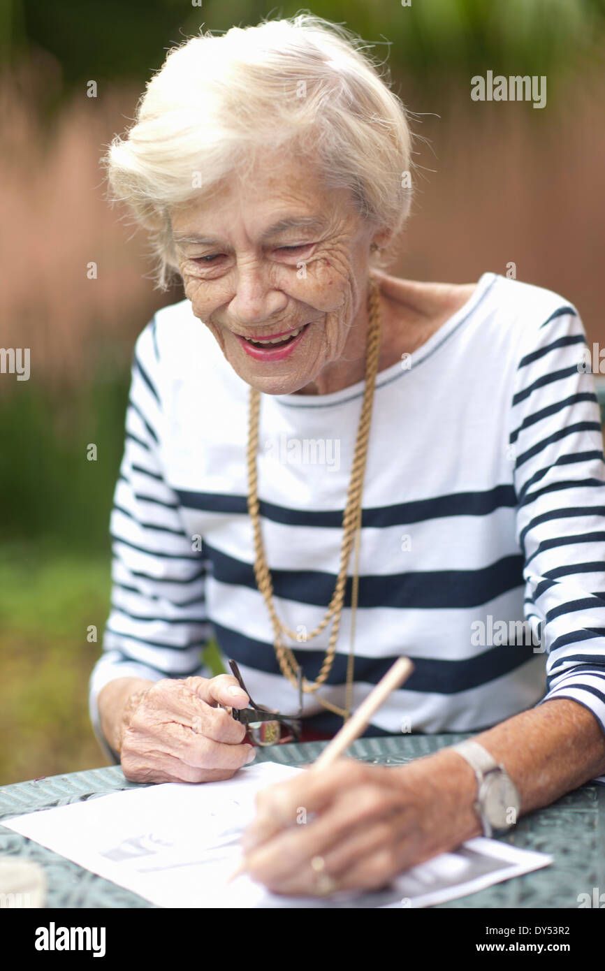 Senior woman drawing in retirement villa garden - Stock Image
