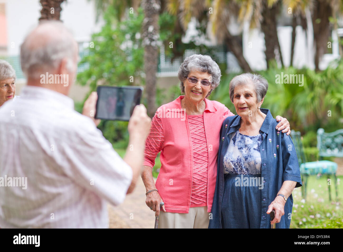 Senior man photographing friends in retirement villa garden - Stock Image