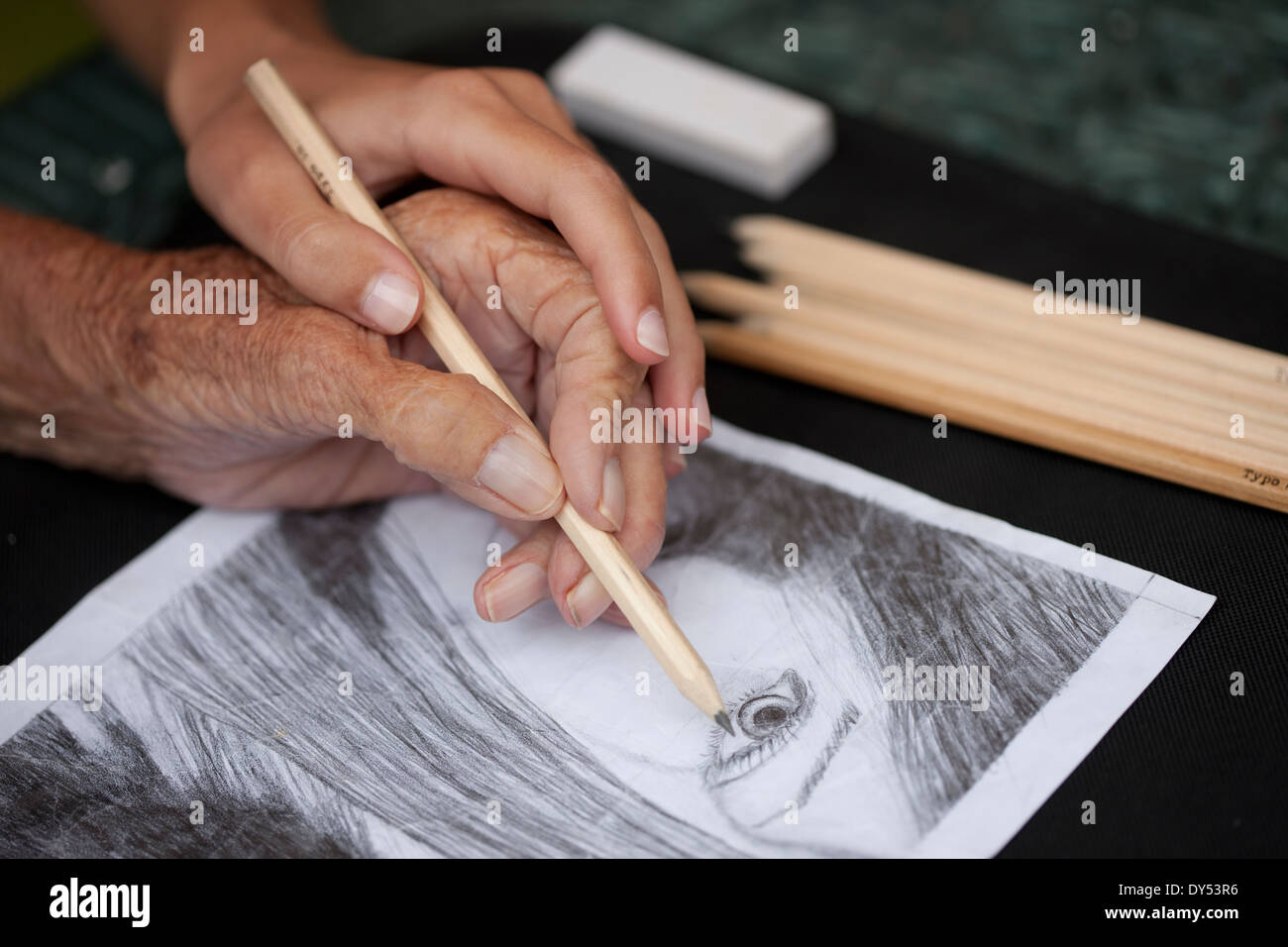 Close up of senior woman's hand doing a pencil drawing - Stock Image