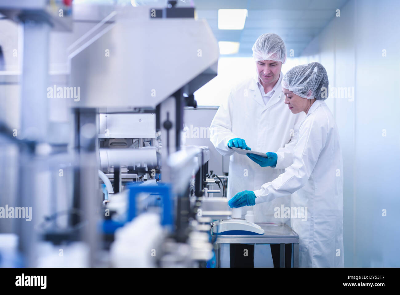 Workers inspecting product in pharmaceutical factory - Stock Image