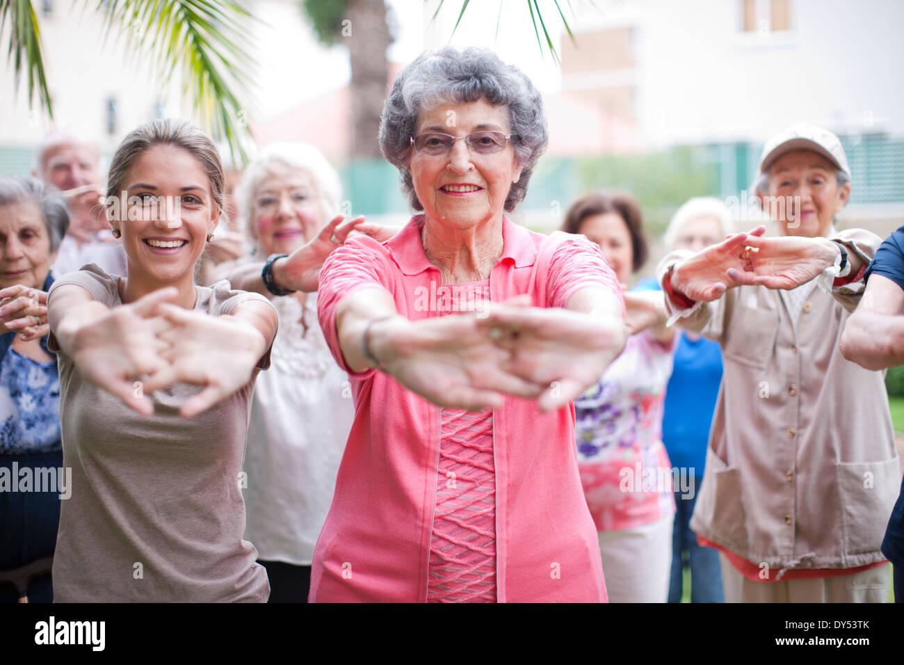 Medium group of seniors exercising in retirement villa garden - Stock Image