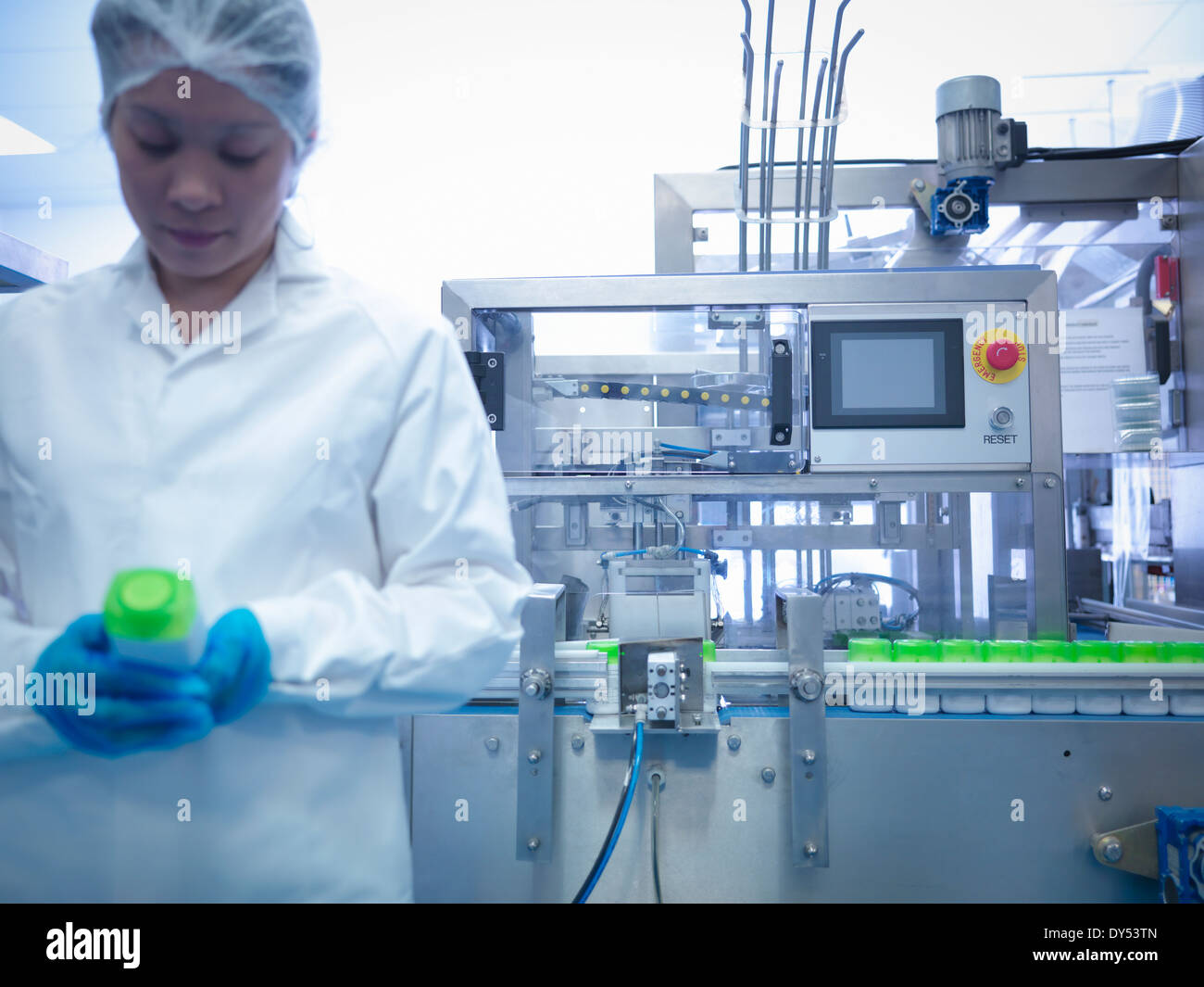 Worker inspecting products on production line in pharmaceutical factory - Stock Image