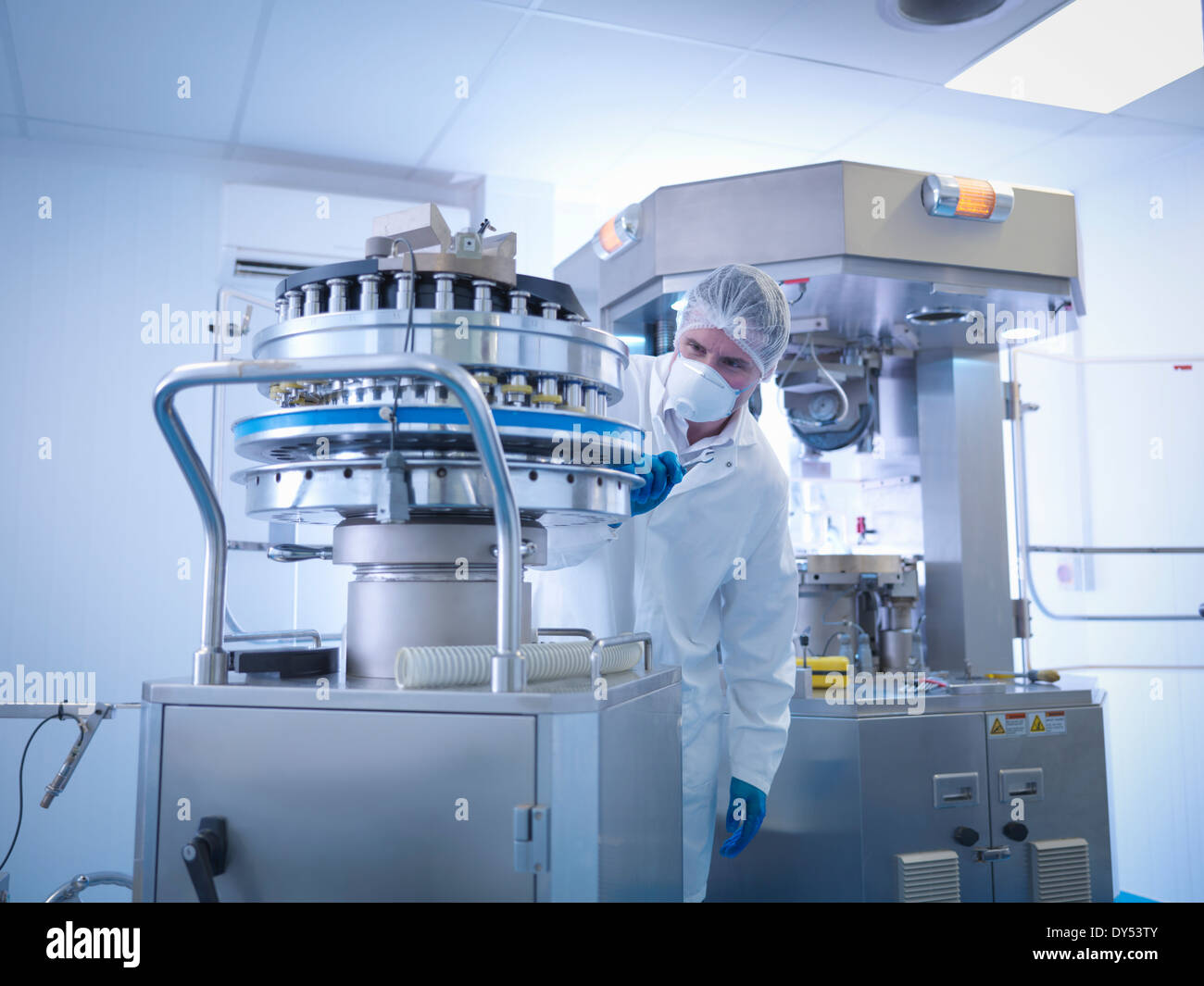 Engineer performing maintenance on tablet manufacturing machine in pharmaceutical factory - Stock Image