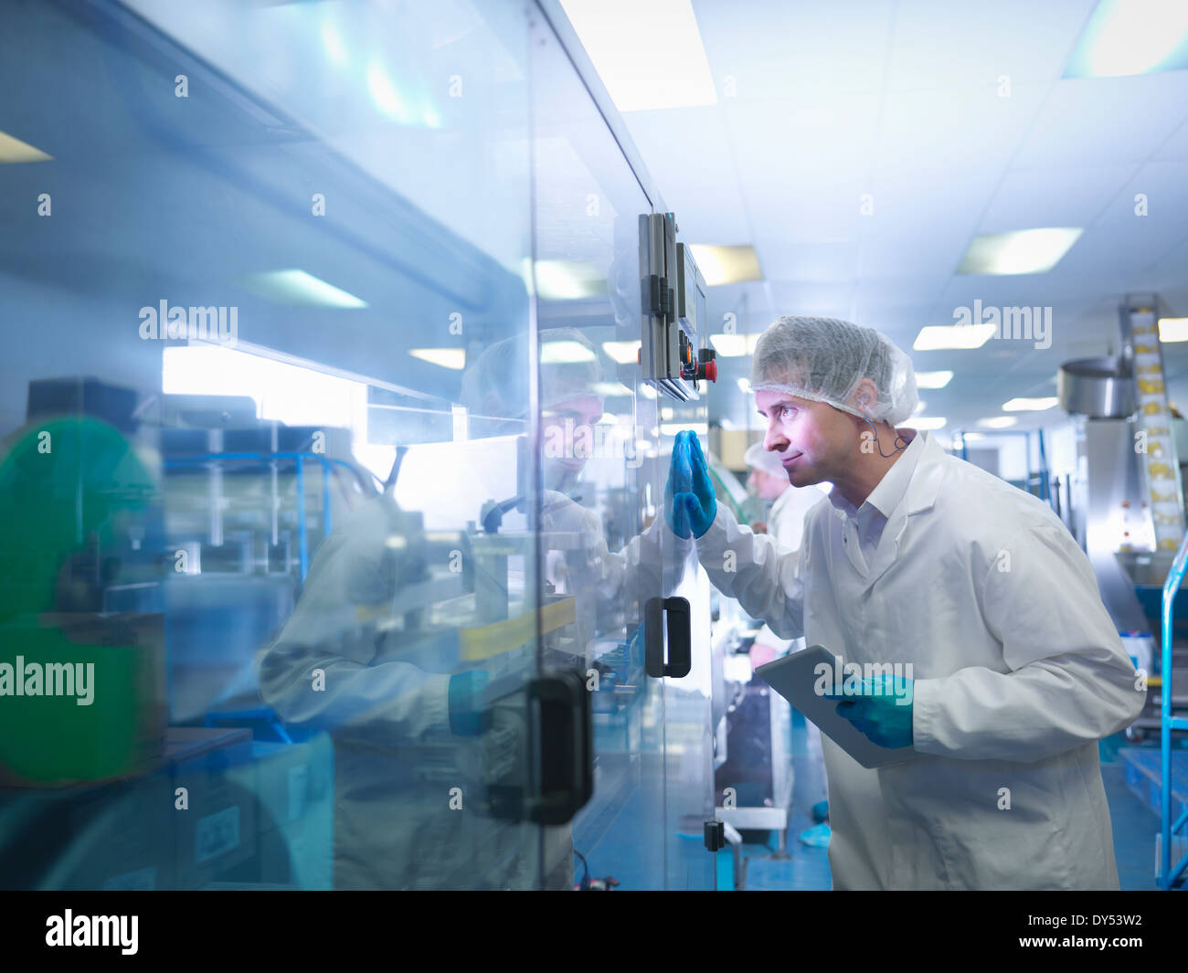 Worker inspecting tablets as they are put into packaging in pharmaceutical factory - Stock Image