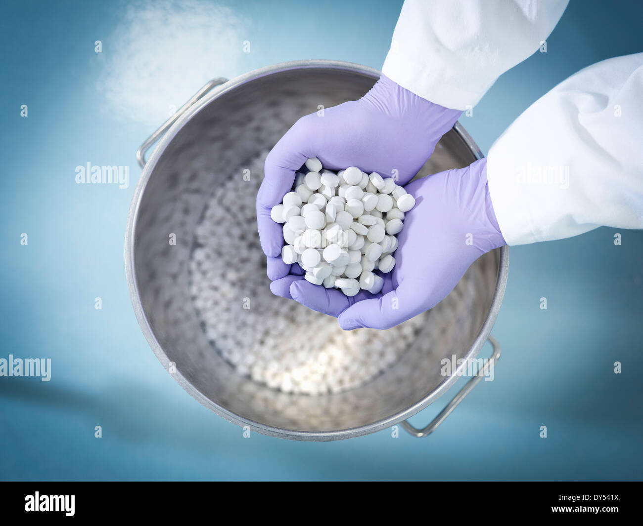 Close up of worker inspecting tablets in pharmaceutical factory - Stock Image