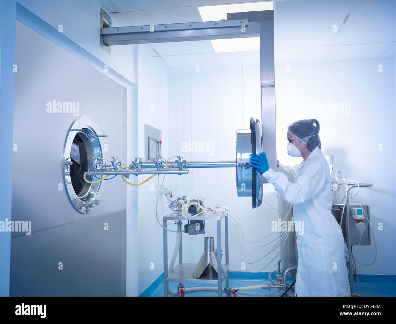 Worker inserting spray jets into tablet coating machine in pharmaceutical factory - Stock Image
